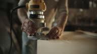Weißen männlichen Tischler in seinen Vierzigern Router ein Stück Holz