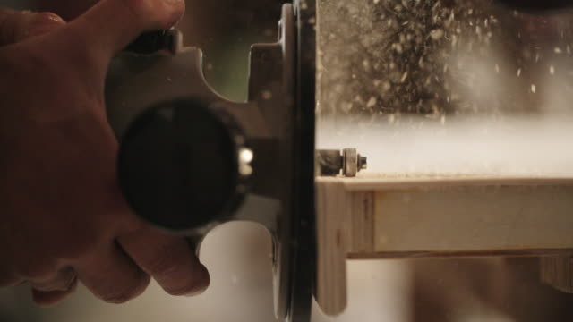White Male Carpenter in his Forties Routers a Piece of Wood