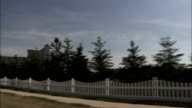A white picket fence stretches alongside a field in between housing developments. Available in HD.