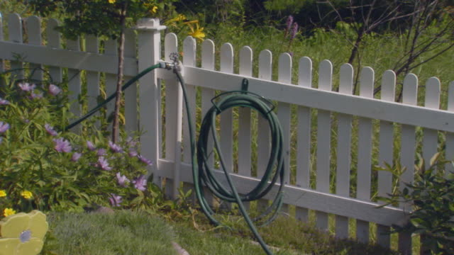 White picket fence with a hose and water spout