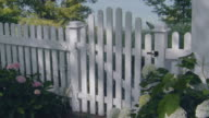 White picket fence with gate leading to water