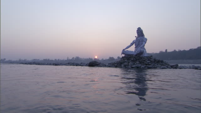 WS POV PAN  White religious statue in mound of rocks in river at sunset / India