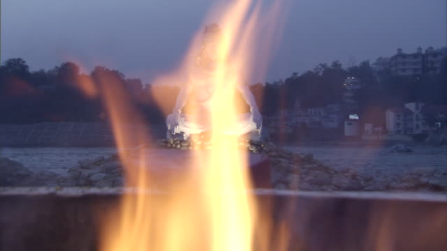MS R/F White religious statue seeing through flames at twilight / India