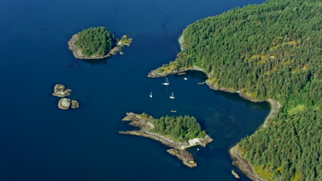 AERIAL White sailboats anchored between the islands and the coast