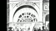 White screen fades into black white painting of Crystal Hall theatre with sign ñ5 cent moving picturesî and people entering / CU sign ñ5 cent moving...