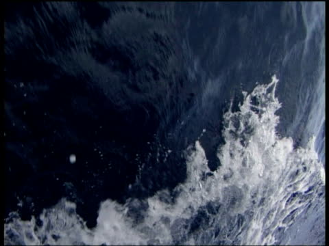 White sea spray thrown up by bow of sailing ship