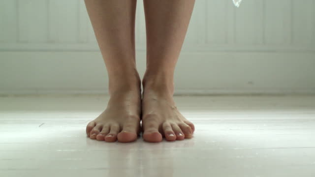 CU White towel falling at woman's feet on bathroom floor, Scarborough, New York, USA