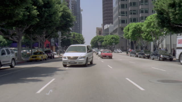 POV White van changing lanes in downtown traffic on busy city street / United States