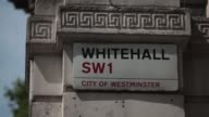 A Whitehall street sign sits on a building wall in London U K on Monday July 15 A street sign sits beyond the iron gates at the entrance to Downing...