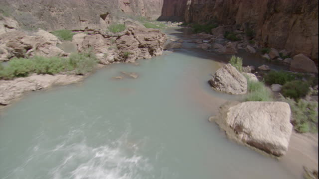 Whitewater flows around rocks in the Colorado River. Available in HD.