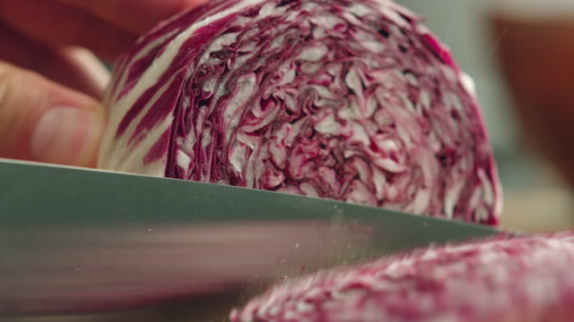 CU Whole organic purple cabbage on kitchen chopping block, Vegetable is sliced with steel knife / Los Angeles, California United States