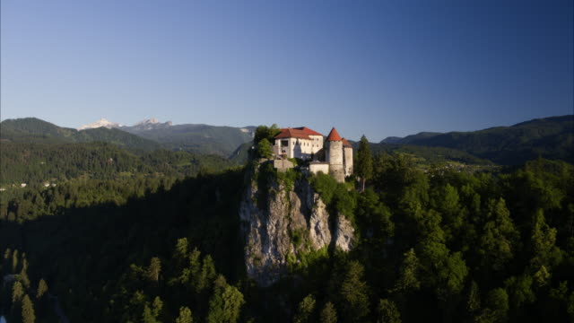 Wide aerial aerial shot of castle on cliff near lake / Bled, Slovenia