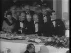 Wide and medium shots of audience at dinner tables / Wide shot of room applauding Vice President Harry A Wallace at podium / Medium shot of Wallace...