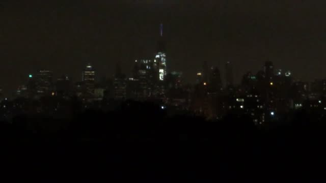 Wide and medium shots of fireworks show over Manhattan taken from Brooklyn