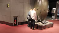 Wide angle at the Atomic Bomb Museum Nagasaki two visitors are reading the description from a replica of the atomic bomb