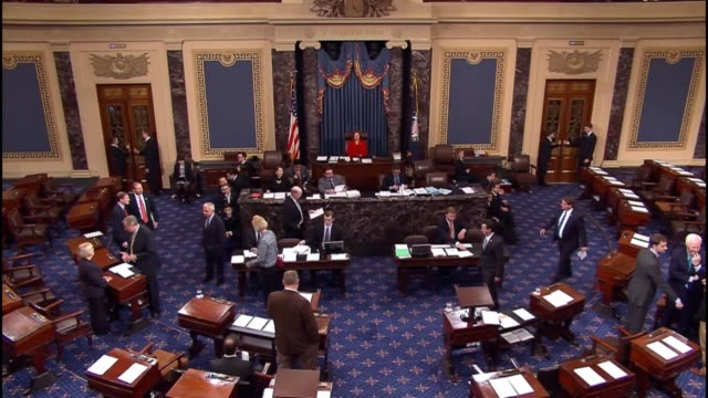 Wide angle footage of the senate floor as senators discuss matters and aides conduct business