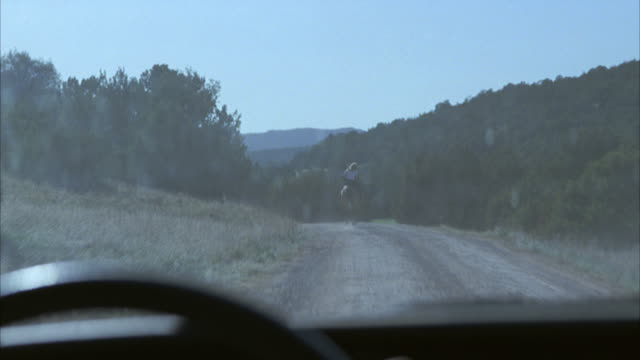 wide angle moving pov from inside of car of man and woman on horseback galloping down dirt road. could be horseback riding. could be chase. could be country road or rural area. trees. mountains in bg. hooves kick up dust. stunt.