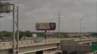 wide angle moving pov of cars and trucks driving on freeway or highway outside of austin. camera focuses on billboard for rum.