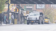 wide angle of black suv driving on city street. suv passes under bridge or overpass and parks. pedestrians visible.