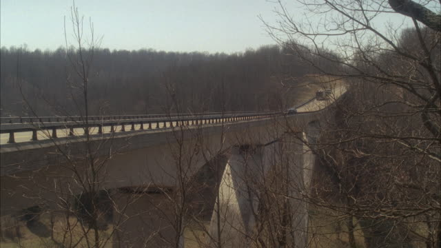 wide angle of cars and tour bus or rv driving on natchez trace parkway bridge through wooded area or forest. bare branches on trees. countryside or rural area.