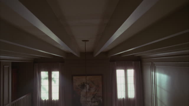 Wide angle of ceiling, with wooden beams running across, of middle or upper class two story house. tall windows with curtains and artwork or painting. decorative molding on walls.