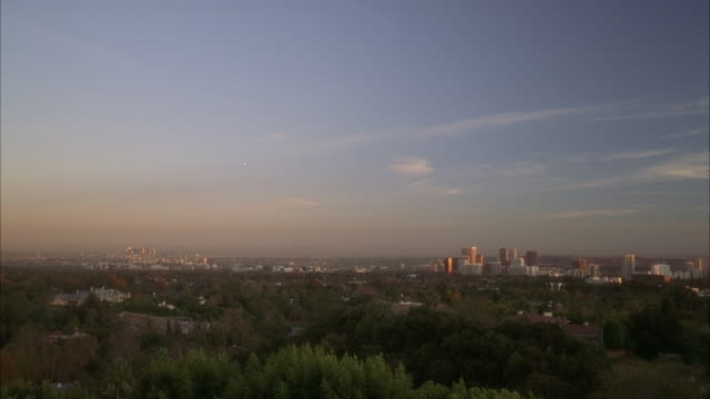 wide angle of city skyline and sunset. could be century city. trees visible in fg. high rises buildings visible in bg.