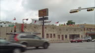 wide angle of city street in austin with boot shop on corner. sign reads allen's boots. stone building on congress st. cars driving on street and stop lights visible.
