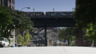 wide angle of el train on bridge or overpass above city street. cars visbile parked on cit street.