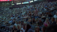 wide angle of people, audience members, spectators in stadium or arena. crowds. could be sporting event or concert.