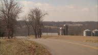 wide angle of pickup truck driving from bg to fg on country road near farmland. could be countryside. barn and silos visible. trees.