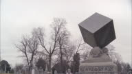 wide angle of stone cube statue, gravestone or memorial. graveyard, cemetery. bare branches on trees. overcast sky.