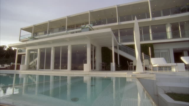 Wide angle of three story upper class house or mansion. could be in hollywood hills. patio and swimming pool.
