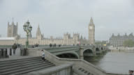 Wide Angle OF WESTMINISTER BRIDGE OVER THAMES RIVER. BIG BEN AND HOUSES OF PARLIAMENT VISIBLE IN BG. TOURISTS, PEDESTRIANS, OR COMMUTERS VISIBLE.