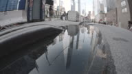 Wide angle shot of New York City's World Trade Center reflected in a puddle.