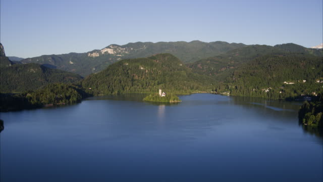 Wide high angle aerial shot approaching distant church on island in lake / Bled, Slovenia