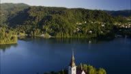 Wide high angle aerial shot of church on island in lake / Bled, Slovenia