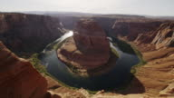 Wide high angle flyover shot of river bend in canyon / Page, Arizona, United States