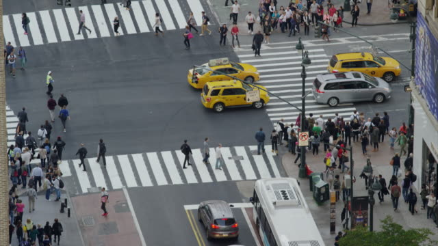 Wide high angle shot of pedestrians in city intersections / New York, New York, United States