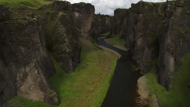 Wide high angle tracking flyover shot of river in canyon / Iceland