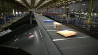 Wide high angle view inside UK Mail Group Plcs letter and parcel sorting center in Birmingham UK on Thursday June 26 Employees walk between conveyor...