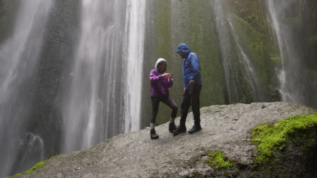 Wide low angle shot of couple standing on rock posing for selfie near waterfall / Rangarvallasysla, Iceland