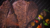 Wide overhead two T-bone steaks on a grill - zoom in to extreme close up of the meat.