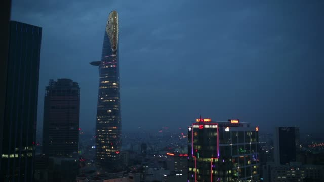 wide pan of city skyline highrises and the Bitexco Financial Tower at night in Ho Chi Minh City Vietnam on Monday June 2 2014