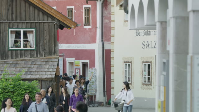 Wide panning shot from busy sidewalk tilting up to houses / Hallstatt, Austria