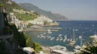 Wide panning shot of boats in harbor / Amalfi, Campania, Italy