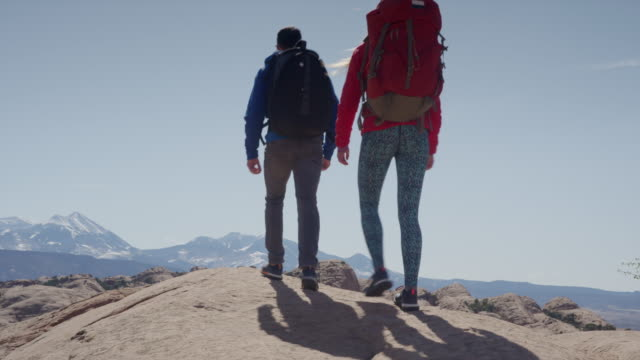Wide panning shot of couple hiking in desert / Moab, Utah, United States