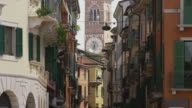 Wide panning shot of crowd in street looking at clock tower / Verona, Italy