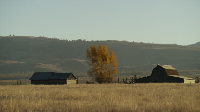 Wide panning shot of farmhouse and barn / Wyoming, United States