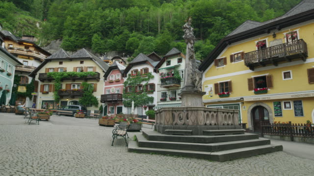 Wide panning shot of fountain in plaza / Hallstatt, Austria