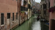 Wide panning shot of gondoliers with tourists in urban canal / Venice, Italy